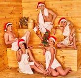 Gruppfolk i jultomtenhatt på bastu Fotografering för Bildbyråer