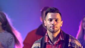Gruppfolk som dansar med lyftta armar till musiken i rökig klubba långsam rörelse stora objekt för bakgrundskontroll mer mycket m lager videofilmer