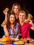 Gruppfolk som rymmer stora hamburgare Royaltyfri Foto