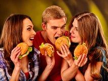 Gruppfolk som rymmer stora hamburgare Arkivbild