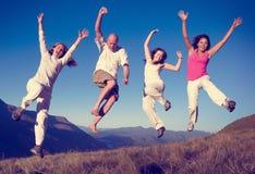 Gruppfolk som utomhus hoppar det Happines begreppet Arkivfoto