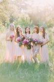 Gruppfotoet av bruden och brudtärnorna som rymmer de enorma rosa buketterna i mitt av den soliga gröna skogen Arkivbild