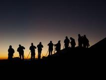 gruppfotografer som skjuter silhouttesoluppgång Royaltyfria Bilder