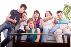 gruppholdingtonåringar tumm upp arkivfoton
