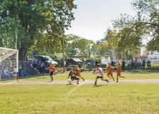 Gruppi dei bambini che giocano a calcio Sunny Day nell'Uruguay Fotografia Stock