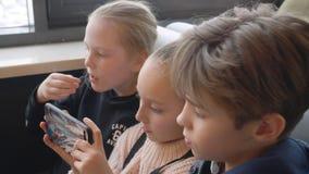 Gruppi dell'adolescente che esaminano telefono cellulare la tavola in caffè degli alimenti a rapida preparazione archivi video