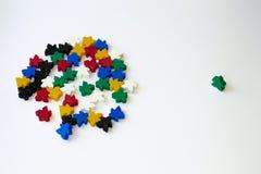 Gruppi di meeples variopinti isolati su fondo bianco Blu, rosso, nero, verde e giallo Piccole figure dell'uomo Giochi da tavolo immagini stock