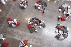 Gruppi di studenti che si siedono in un atrio moderno dell'università fotografia stock