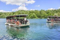 Gruppi di turisti sulle barche che girano lungo i laghi Plitvice Fotografie Stock Libere da Diritti