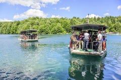 Gruppi di turisti sulle barche che girano lungo i laghi Plitvice Fotografia Stock Libera da Diritti