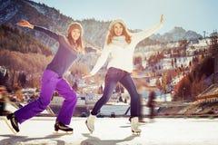 Gruppieren Sie den lustigen Jugendlichmädcheneislauf, der an der Eisbahn im Freien ist Stockfoto