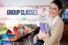 Gruppieren Sie Klassen gegen den hübschen Lehrer, der an der Kamera an der Rückseite des Klassenzimmers lächelt lizenzfreie stockfotos