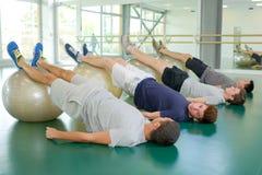 Gruppieren Sie Männer mit den Beinen, die auf aerobe Bälle angehoben werden Lizenzfreie Stockfotos