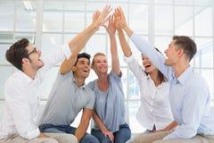 Gruppieren Sie Therapie in der Sitzung, die in einem hoch fiving Kreis sitzt Lizenzfreie Stockfotos