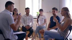 Gruppieren Sie Therapie, die jungen Leute mit Ausweisen sprechend zusammen mit dem Psychologen, der auf Stühlen sitzt