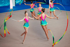 Gruppkapacitetsgymnaster övar med band Arkivfoto