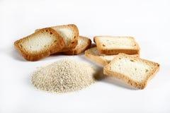 Gruppkexar och brödsmulor på vit Arkivbilder