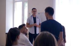 Gruppkurser, ledareman diskuterar med kollegaproblemlägen på lagutbildning i indoods stock video