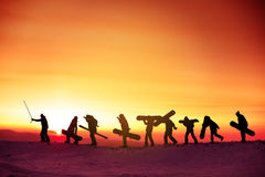 Grupplagsnowboarderen skidar begreppssolnedgången royaltyfri bild