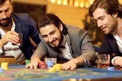 Gruppman i en dräkt på tabellrouletten som spelar poker på en kasino royaltyfri fotografi