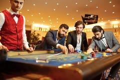 Gruppman i en dräkt på tabellrouletten som spelar poker på en kasino royaltyfri bild