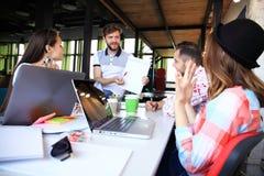 Gruppmedlemmar som uppmärksamt lyssnar till en gladlynt affärsman som rymmer en presentation royaltyfri fotografi