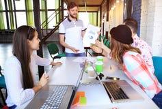 Gruppmedlemmar som uppmärksamt lyssnar till en gladlynt affärsman som rymmer en presentation royaltyfri foto