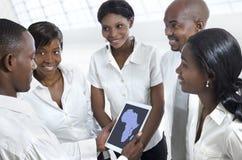 Gruppo africano di affari che discute con il PC della compressa Fotografia Stock