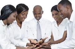 Gruppo africano di affari che presenta con le mani aperte Immagini Stock