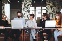 Gruppo allegro dei colleghe che lavorano insieme nello spazio moderno del sottotetto sulla tavola di legno con il computer portat Immagine Stock