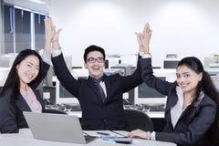 Gruppo allegro di affari che tosta le mani Immagini Stock Libere da Diritti