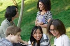 Gruppo allegro di giovani studenti che si siedono e che studiano Fotografia Stock