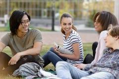 Gruppo allegro di studenti multietnici che studiano all'aperto Immagine Stock
