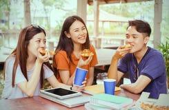 Gruppo asiatico che mangia insieme pizza nella rottura del tempo fotografia stock libera da diritti
