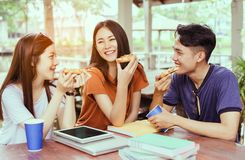 Gruppo asiatico degli studenti che mangia insieme pizza nella rottura del tempo fotografia stock libera da diritti