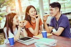 Gruppo asiatico degli studenti che mangia insieme pizza nella rottura del tempo fotografia stock
