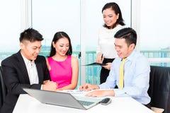 Gruppo asiatico del banchiere che consiglia le coppie in ufficio immagine stock