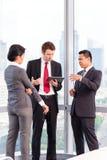 Gruppo asiatico di affari - orizzonte urbano Immagine Stock
