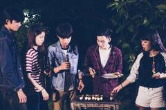 Gruppo asiatico di amici che hanno barbecue all'aperto del giardino che ride w Immagini Stock