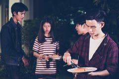 Gruppo asiatico di amici che hanno barbecue all'aperto del giardino che ride w Immagine Stock