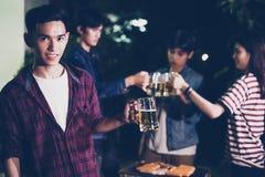 Gruppo asiatico di amici che hanno barbecue all'aperto del giardino che ride w Fotografie Stock Libere da Diritti