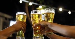 Gruppo asiatico di amici che hanno partito con le bevande alcoliche della birra ed i giovani che godono ad una barra che tosta i  immagine stock