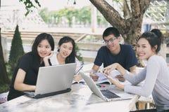 Gruppo asiatico di studenti che per mezzo della compressa e del taccuino che dividono con la t Fotografie Stock