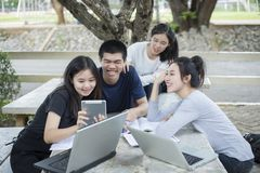 Gruppo asiatico di studenti che per mezzo della compressa e del taccuino che dividono con la t Immagine Stock Libera da Diritti