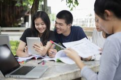 Gruppo asiatico di studenti che per mezzo della compressa e del taccuino che dividono con la t Fotografia Stock Libera da Diritti