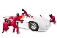 Gruppo che mantiene servizio tecnico alla fermata del pozzo per una vettura da corsa Fotografie Stock