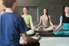 Gruppo con l'istruttore di yoga nel club di forma fisica Fotografie Stock