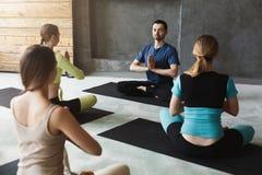 Gruppo con l'istruttore di yoga nel club di forma fisica Immagine Stock