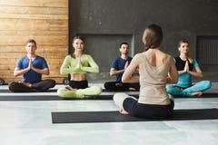 Gruppo con l'istruttore di yoga nel club di forma fisica Immagini Stock