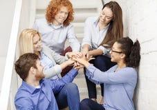 Gruppo con le mani sopra a vicenda sulla scala Immagini Stock
